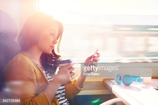 Woman on a commuter train looking at her phone. : Foto de stock