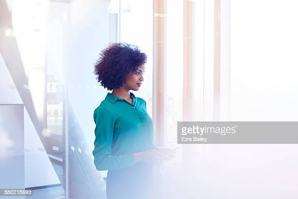 Businesswoman looking out of window in thought