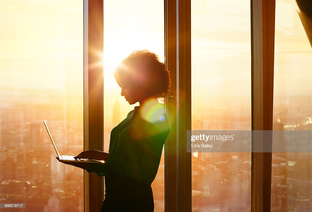 Businesswoman on laptop at window in morning sun : Stock Photo