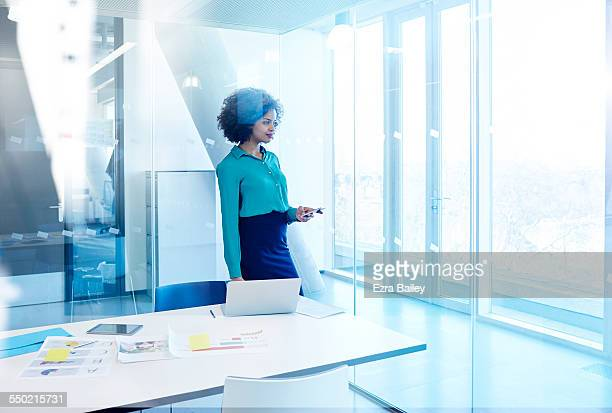 Businesswoman checking emails at window