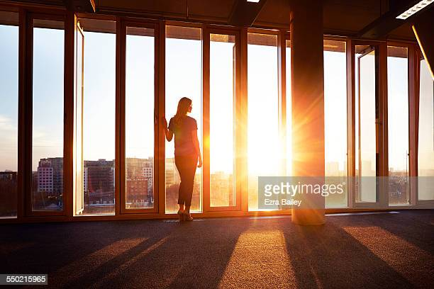 Businesswoman looks across city at sunrise