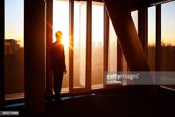 Businessman looks out at city sunrise.