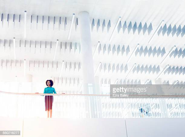 Businesswoman looking out across modern office
