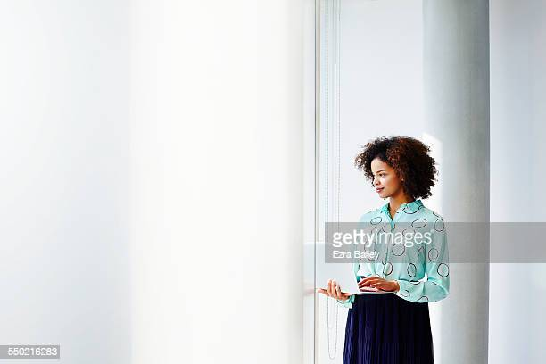 Businesswoman with laptop looking out of window.