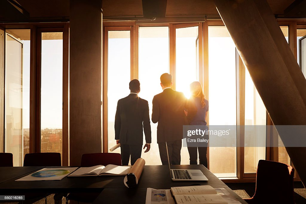 Colleagues looking out across city at sunrise : Stock Photo