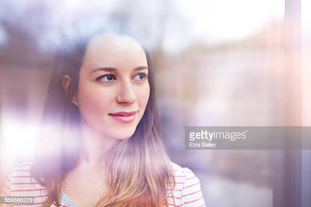 Young woman gazes thoughtfully through window