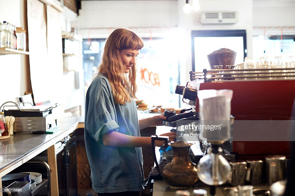 Small business owner works behind cafe counter : Stock Photo