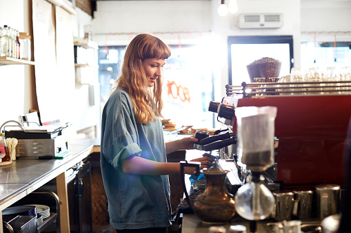 Small business owner works behind cafe counter