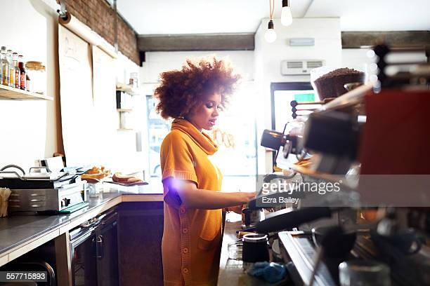 Girl working behind cafe counter in coffee shop