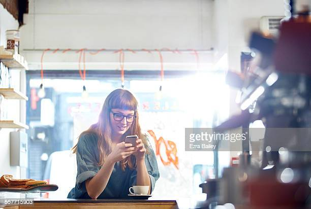 Girl relaxes with coffee while checking her phone