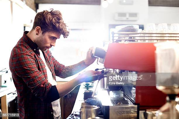 Barista prepares coffee in trendy coffee shop