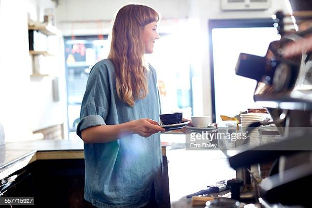 Girl smiles and chats as she serves coffee