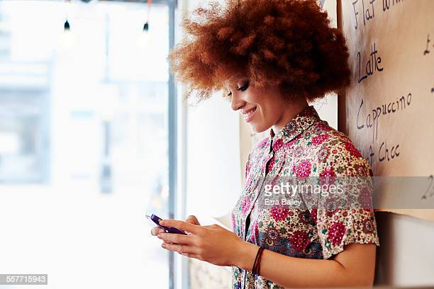 Girl in coffee shop smiling looking at her phone