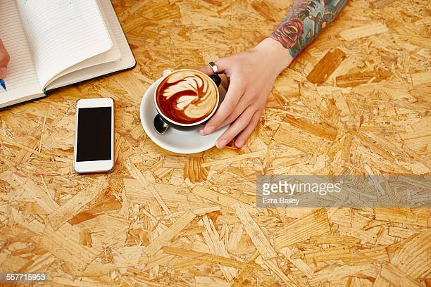 Guy with arm tattoo holds coffee and writes notes
