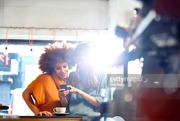 Two girls look at phone together in coffee shop