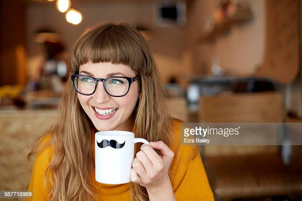 Girl smiles drinking out of moustache mug