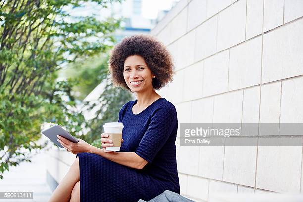 Businesswoman sits outside with coffee and tablet