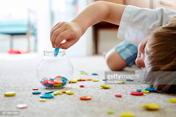 Young child playing with multi coloured buttons.