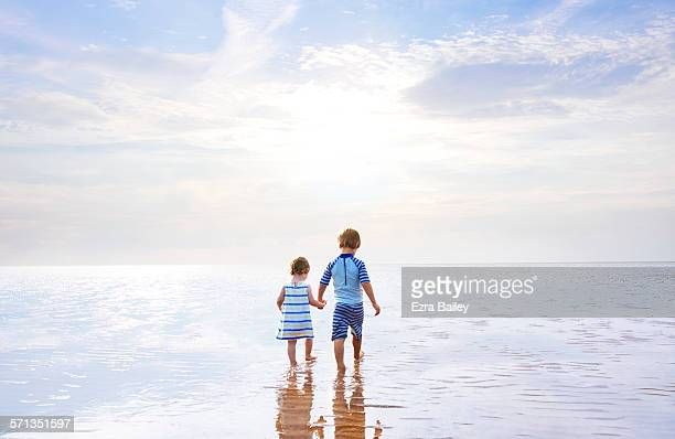 Brother and sister holding hand walking out to sea