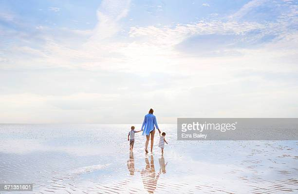 Mother and children walking at low tide sunset.