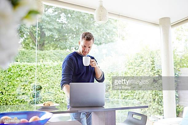 Man works on a laptop in kitchen with a coffee