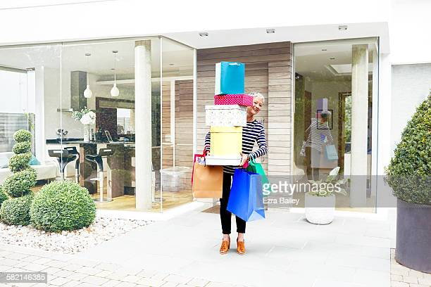 Woman laughing peeping out behind all her shopping