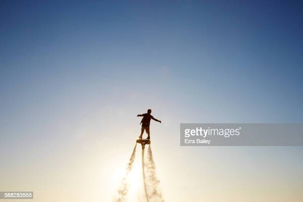 Man flyboarding at sunset