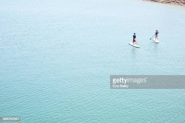 Couple paddleboarding in the sun.