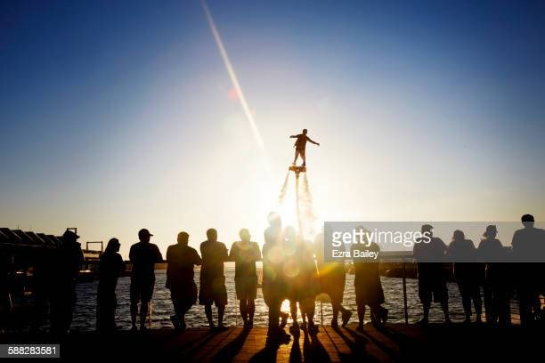 Man flyboarding at sunset in front of a crowd.