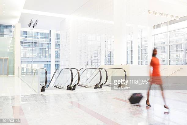 Businesswoman walks through large modern space.
