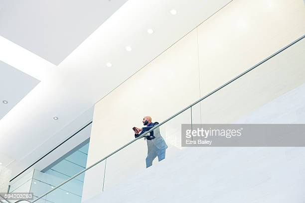 Businessman looking out from a balcony.