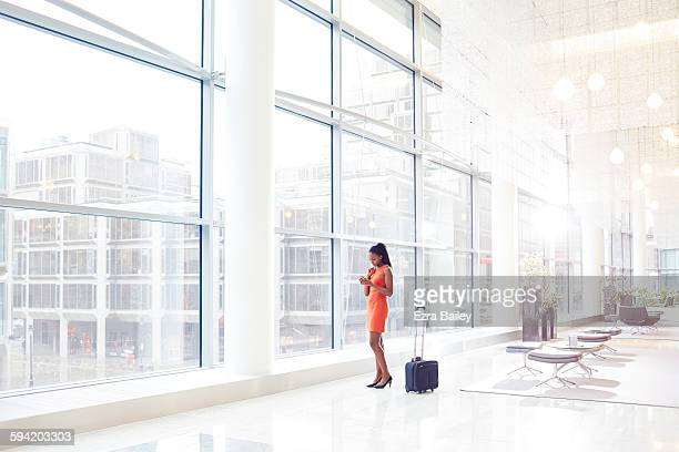 Businesswoman in modern office checking her phone.