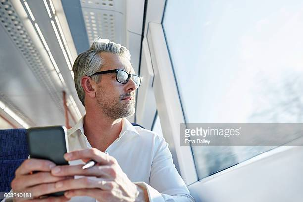 Businessman looking out the window on a train.