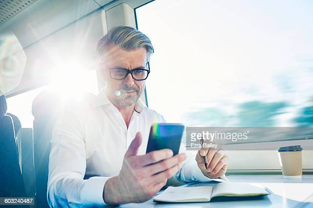 Businessman checking his phone while commuting.
