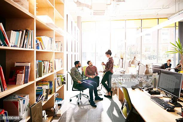 Creative coworkers chatting over ideas in office