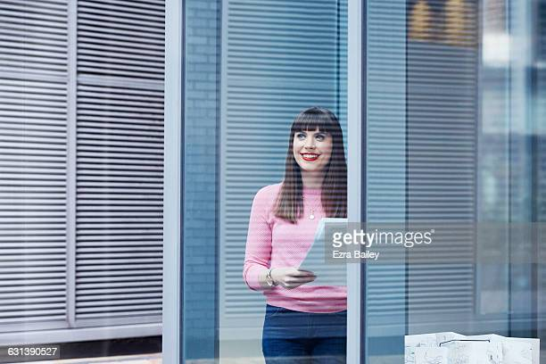 Office worker smiles as she looks out of window