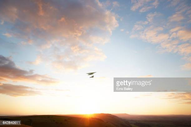 Hang glider flying over hills at sunset