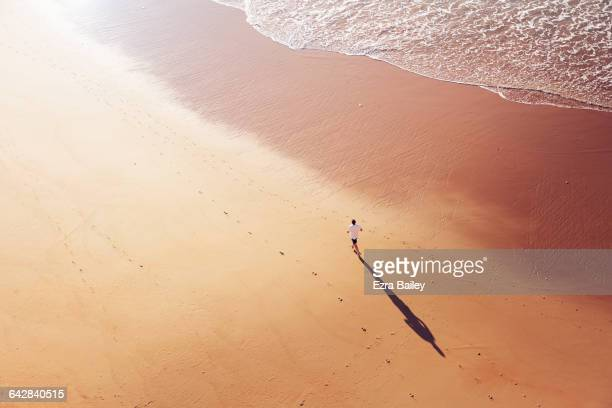 Man running along the shoreline at sunrise