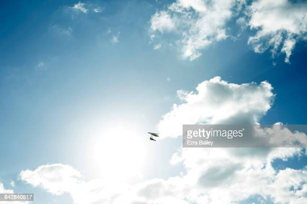 Hand glider flying across sun and clouds