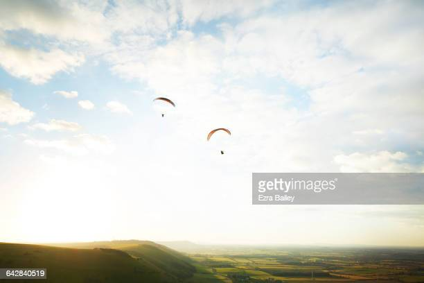 Two paragliders flying high above the hills