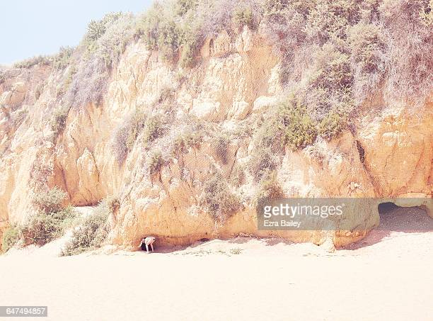 Girl looking into a small cave.
