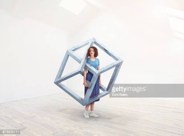 Woman interacting with an impossible cube.