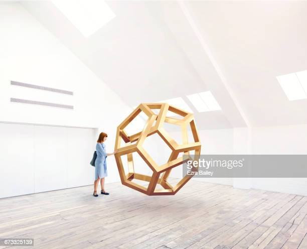 Woman interacting with an impossible shape.