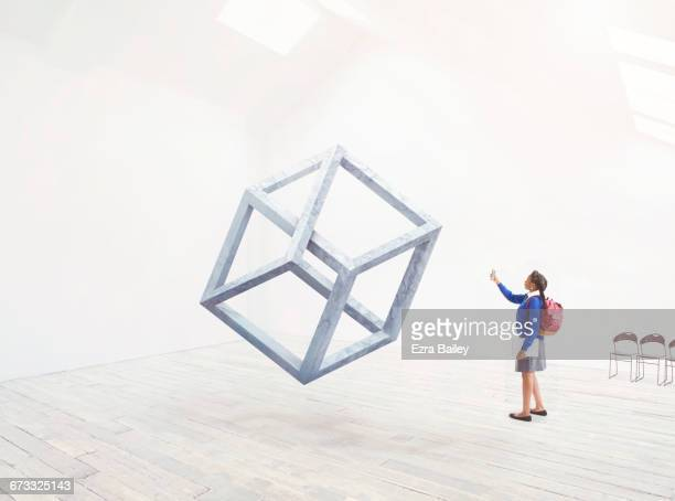 School girl taking a photo of an Impossible cube.
