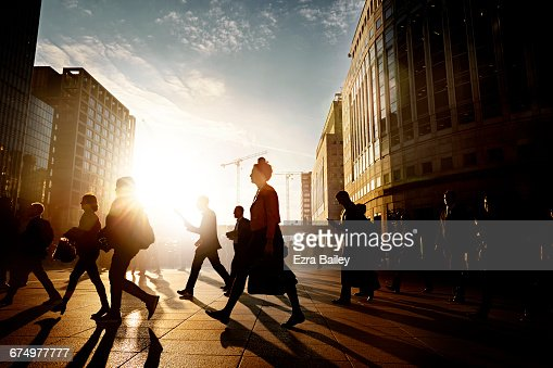 Employees walking to work in the city at sunrise : Stock Photo