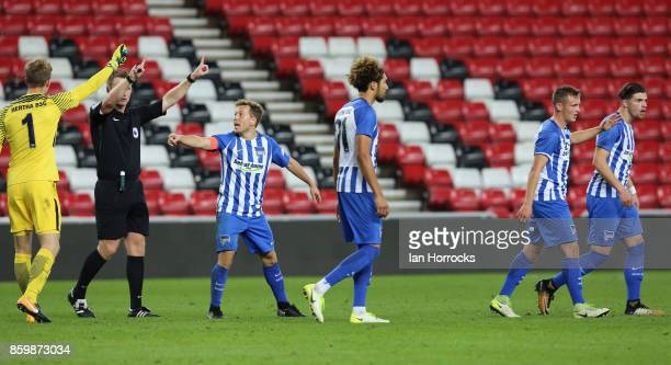 f Hertha Berlin players are asked to leave the field after a angry end to the game during the Premier League International Cup match between...