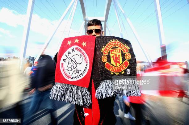 A faan with a half and half scarf is seen near the stadium prior to the UEFA Europa League Final between Ajax and Manchester United at Friends Arena...
