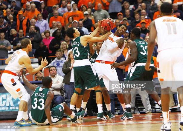 Fab Melo of the Syracuse Orange holds the ball against Emmy Andujar and Rhamel Brown of the Manhattan College Jaspers during the NIT Season Tipoff at...