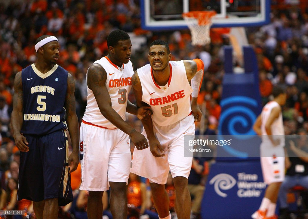 <a gi-track='captionPersonalityLinkClicked' href=/galleries/search?phrase=Fab+Melo&family=editorial&specificpeople=7366439 ng-click='$event.stopPropagation()'>Fab Melo</a> #51 of the Syracuse Orange limps off the court after an injury as he is assisted by teammate <a gi-track='captionPersonalityLinkClicked' href=/galleries/search?phrase=Dion+Waiters&family=editorial&specificpeople=6902921 ng-click='$event.stopPropagation()'>Dion Waiters</a> #3 as Bryan Bynes #5 of the George Washington Colonials looks on in between play at the Carrier Dome on December 10, 2011 in Syracuse, New York.