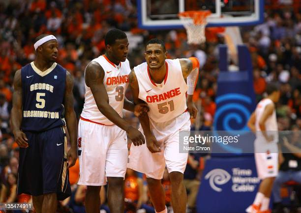 Fab Melo of the Syracuse Orange limps off the court after an injury as he is assisted by teammate Dion Waiters as Bryan Bynes of the George...